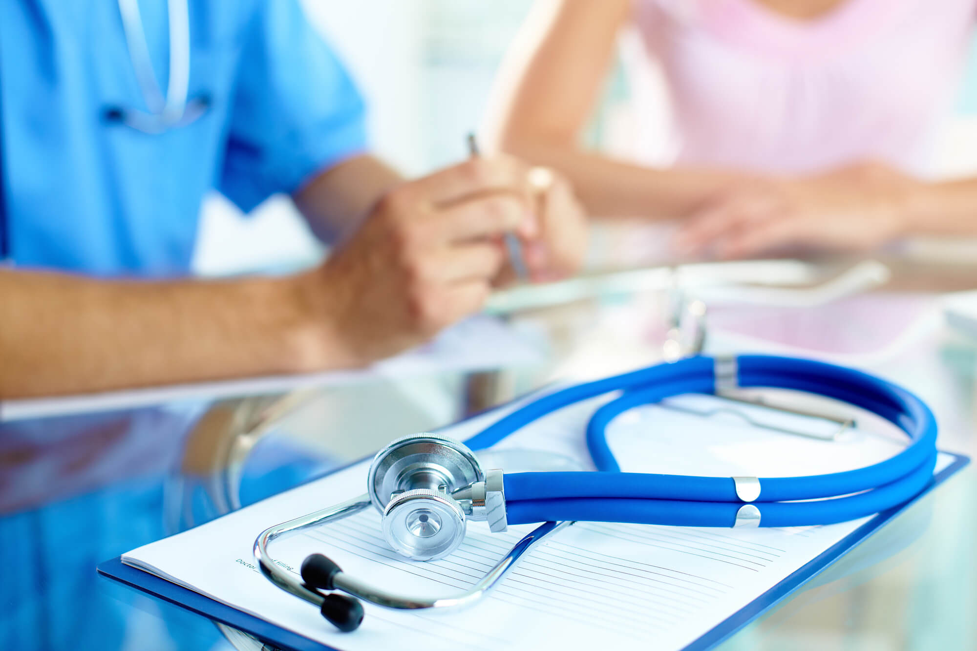 staff consulting a patient with a stethoscope on the table Doctor office job recruiters
