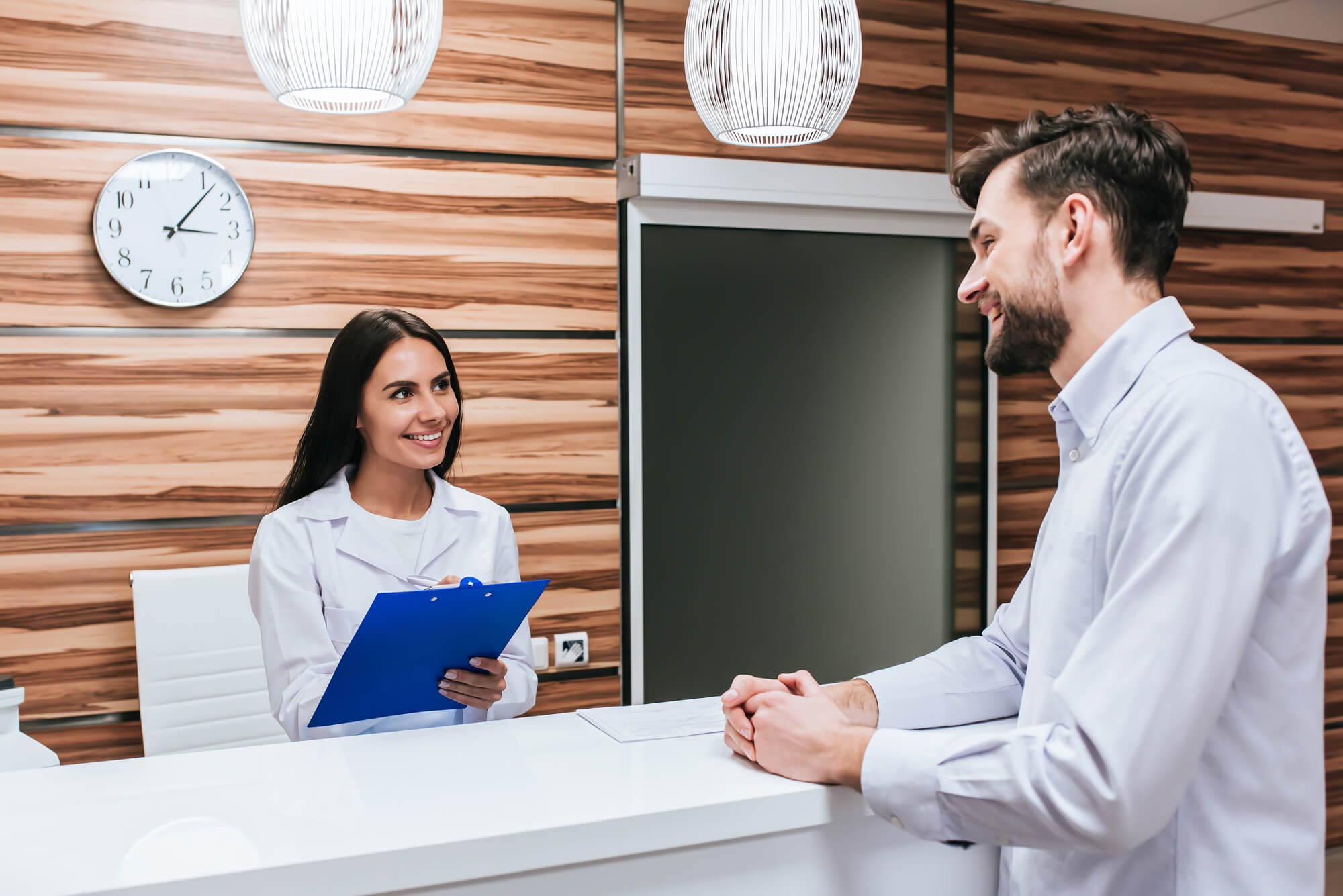 doctor's staff talking to a patient in the counter Doctor office job recruiters