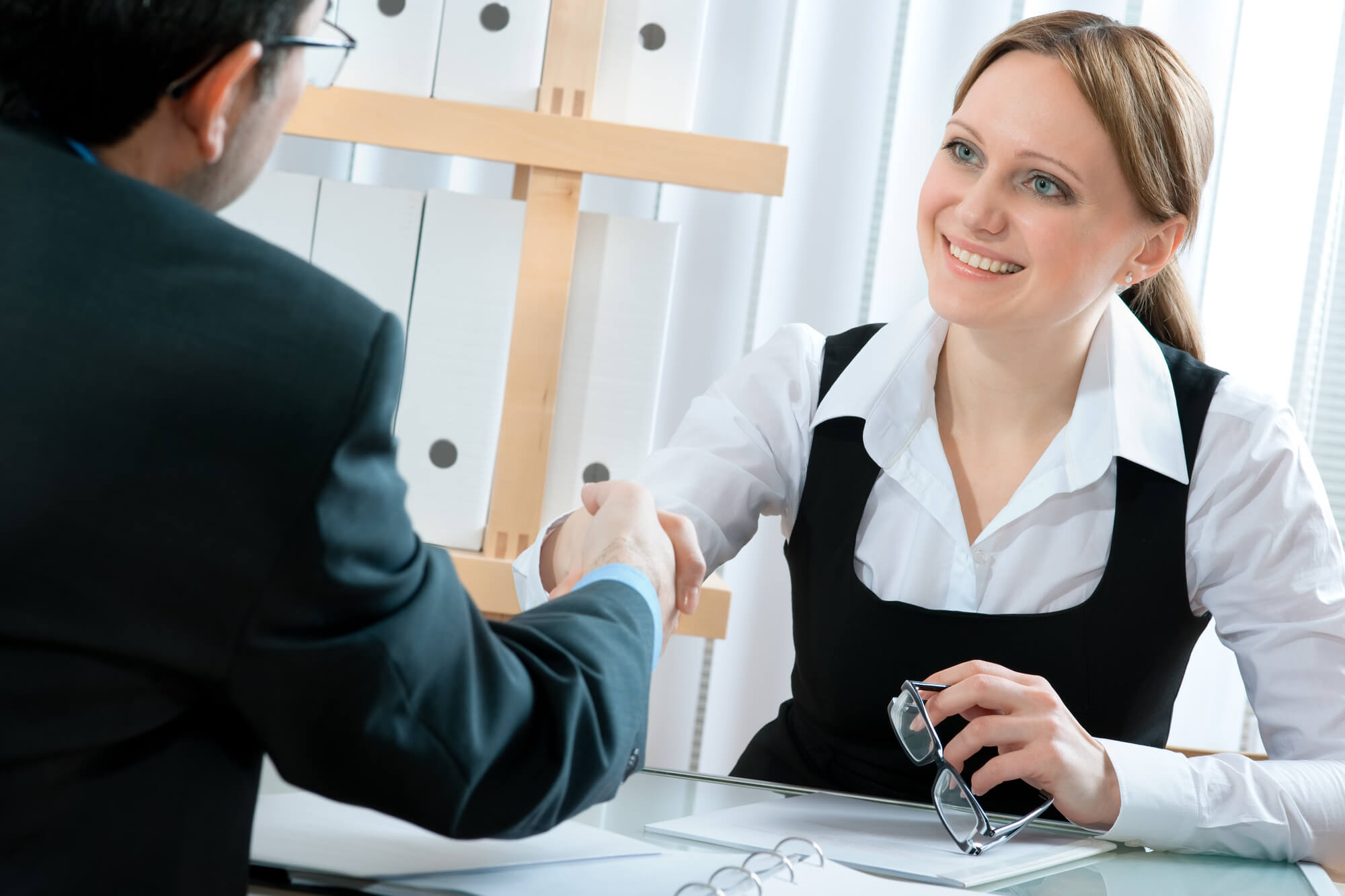 businesswoman shaking the hand of an applicant orthodontics positions hiring
